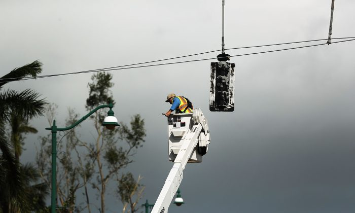 An electrical worker repairs stop lights the morning after Hurricane Irma swept through Naples, Florida on September 11, 2017 (Spencer Platt/Getty Images)