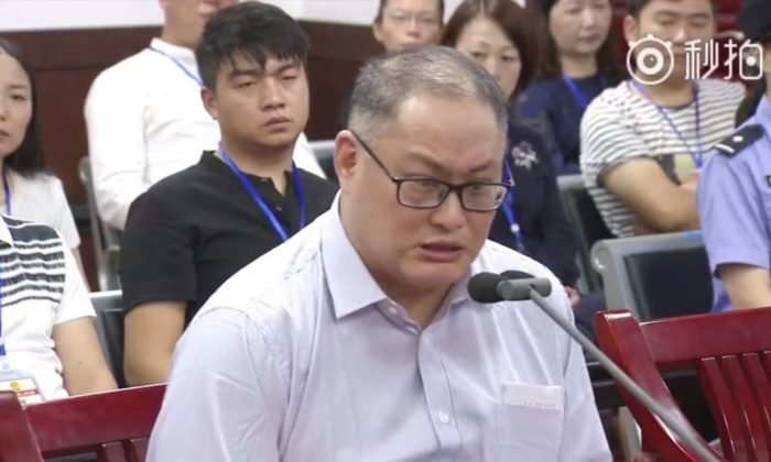 "In a video released by the Chinese court, a visibly shaken Lee Ming-che can be seen reading out a statement in court that admits his guilt for ""subverting"" the Chinse government. Lee's wife can be seen sitting in the last row of the court room. (Weibo Screenshot/Yueyang Intermediate People's Court)"