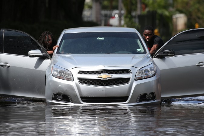 People push a flooded car off a street following Hurricane Irma in North Miami, Florida on Sept. 11, 2017. (Reuters/Carlo Allegri)