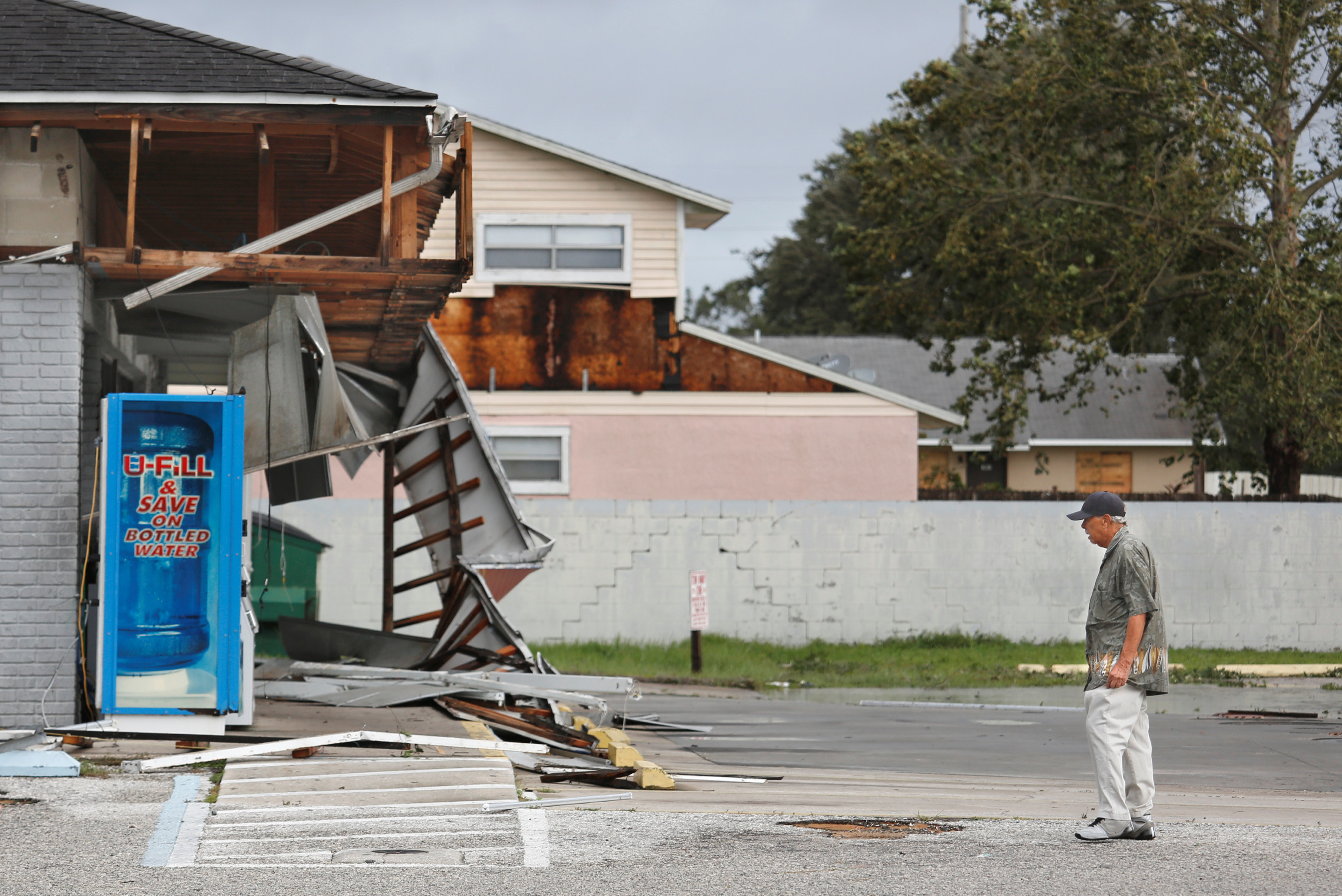 A local resident observes the remains of a Sunoco gas station in the wake of Hurricane Irma in Kissimmee, Florida on Sept. 11, 2017. (REUTERS/Gregg Newton)