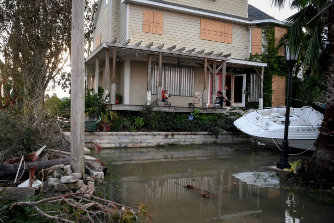 Residents sit on their front porch watching water reside after Hurricane Irma in Everglades City, Florida, on Sept. 11, 2017. (REUTERS/Bryan Woolston)