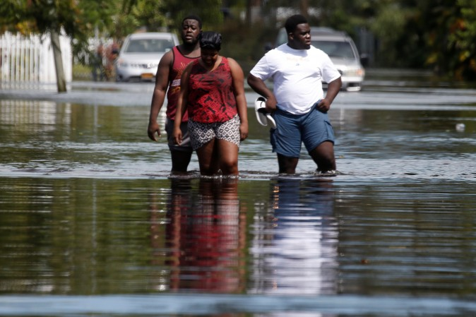 People walk on a flooded street following Hurricane Irma in North Miami, Florida on Sept. 11, 2017. (REUTERS/Carlo Allegri)