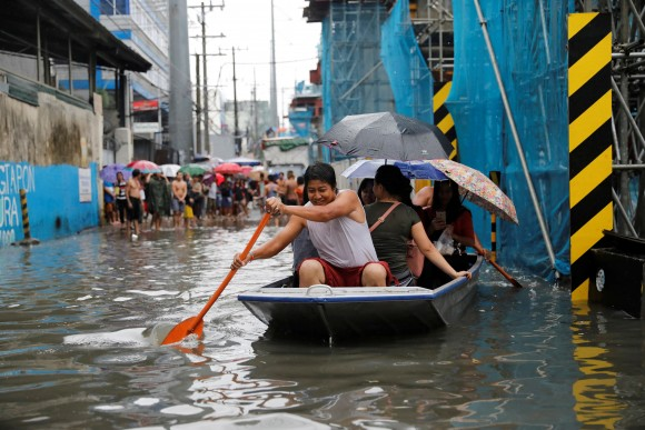 Residents use a makeshift boat to ferry commuters along floodwaters in Quezon City, Metro Manila as a storm sweeps across the main Luzon island, Philippines, September 12, 2017. (Reuters/Dondi Tawatao)