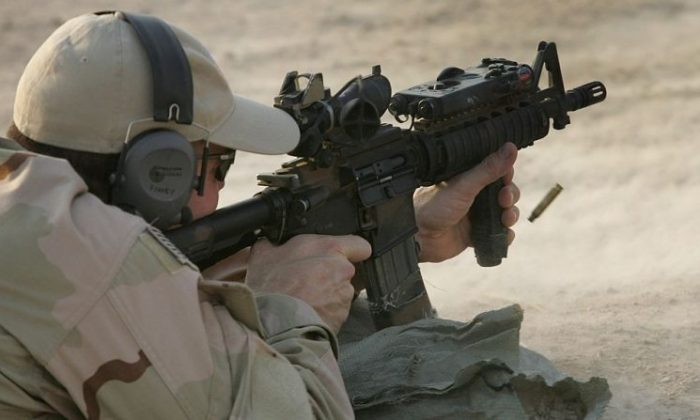 A U.S. Navy SEAL fires his M-4 assault rifle during a training session with Iraqi army scouts July 26, 2007, in Fallujah, Iraq. (John Moore/Getty Images)