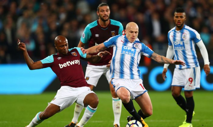 Andre Ayew of West Ham United and Aaron Mooy of Huddersfield Town battle for the ball during the Premier League match between West Ham United and Huddersfield Town at London Stadium on Sept 11, 2017 in London, England. (Clive Rose/Getty Images)