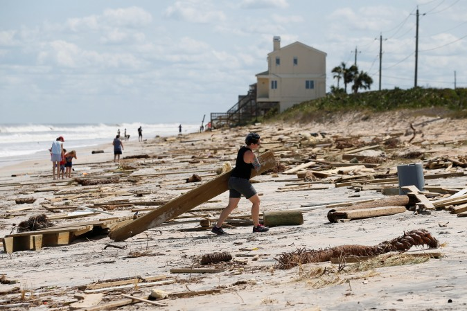 A woman clears debris from the beach after Hurricane Irma passed the area in Ponte Vedra Beach, Florida, U.S., September 12, 2017. (Reuters/Chris Wattie)