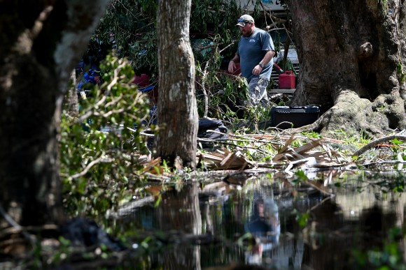 Carl Nicholson cleans debris and fallen trees from his flooded yard following Hurricane Irma near Jerome, Florida, U.S., September 12, 2017. (Reuters/Bryan Woolston)