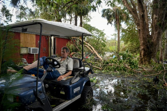 Robert Market, 82, sits in a golf cart in his front yard filled with fallen trees, flood waters, and debris, following Hurricane Irma, near Jerome, Florida, U.S., September 12, 2017. (Reuters/Bryan Woolston)