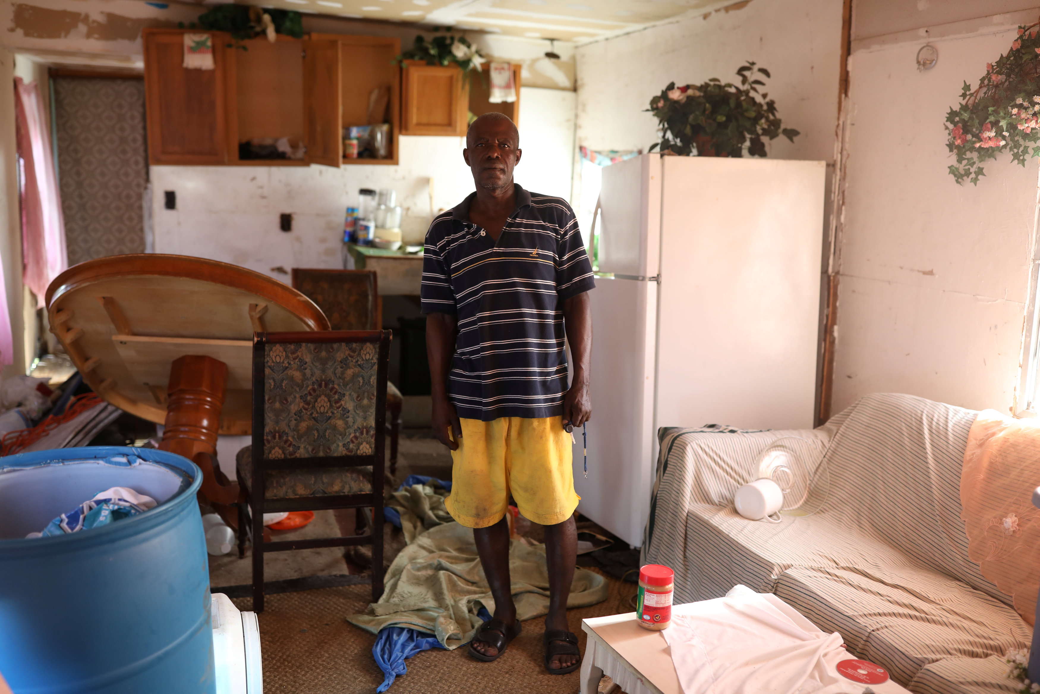 Renel Madere stands inside his mobile home, which was damaged by Hurricane Irma in Immokalee, Florida, U.S. September 12, 2017 (Reuters/Stephen Yang)