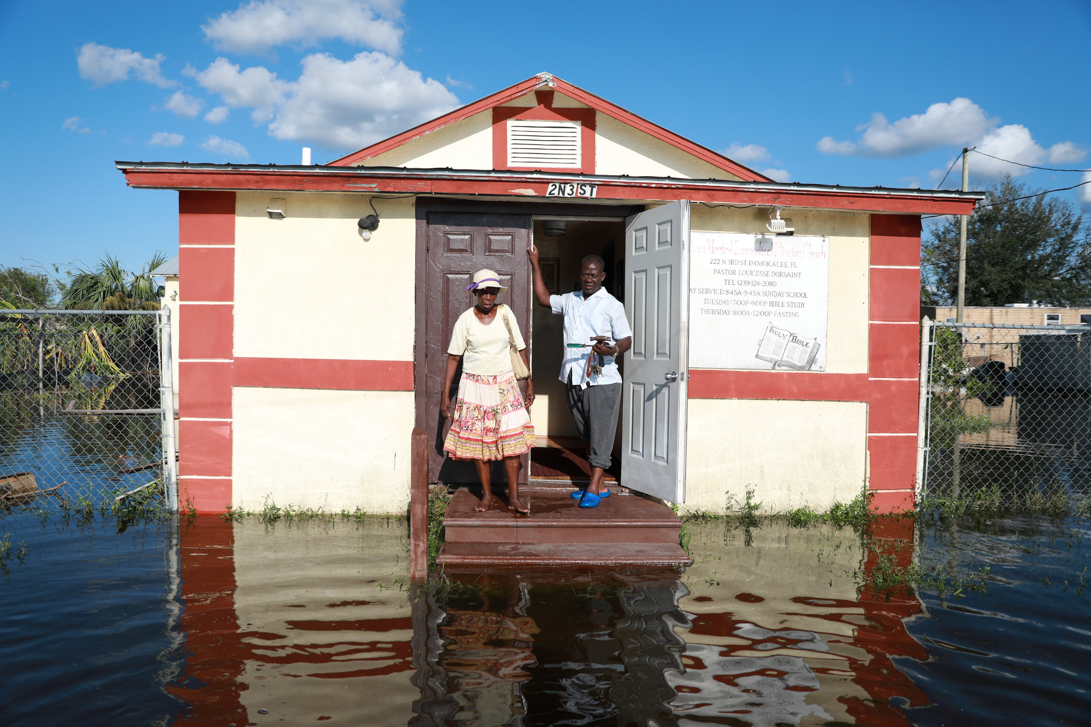 Pastor Louicesse Dorsaint stands with his wife Maria Dorsaint in front of their church, Haitian United Evangelical Mission, which was damaged by flooding from Hurricane Irma in Immokalee, Florida on Sept. 12, 2017. (Reuters/Stephen Yang)