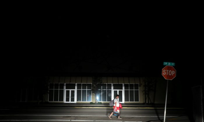 A man walks back home in the darkness as many areas of Miami still without electricity after Hurricane Irma strikes Florida, in Little Havana, Miami, Florida on Sept. 11, 2017. (REUTERS/Carlos Barria)