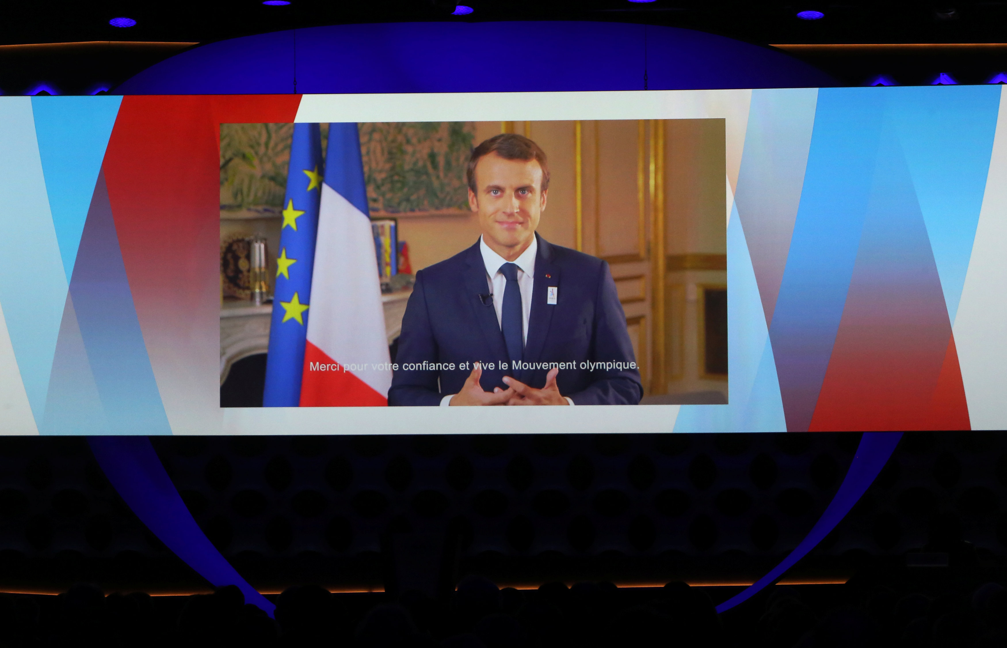 France's President Emmanuel Macron is seen on a screen as he delivers a video speech at the presentation of Paris 2024 at the 131st IOC session in Lima, Peru on Sept. 13, 2017. (REUTERS/Mariana Bazo)