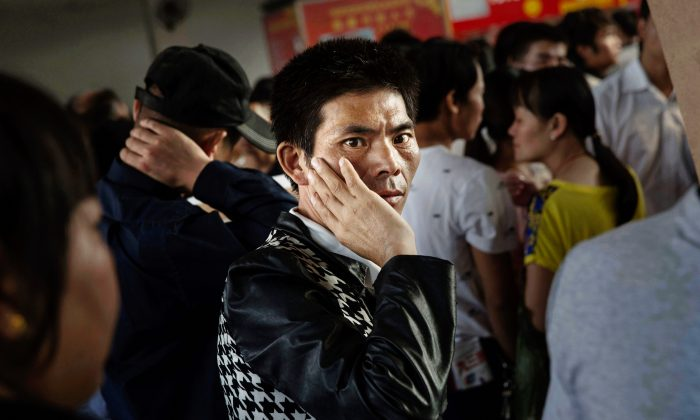 A Chinese man stands inside a job center on September 18, 2015 in Yiwu, Zhejiang Province, China in 2015. China's slower economy has left many desperate for work, making them vulnerable to pyramid schemes that are evolving into criminal syndicates. (Kevin Frayer/Getty Images)