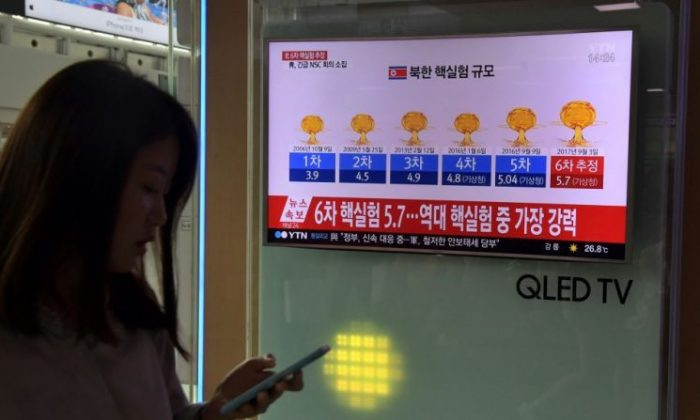 A woman by a television display at a train station in Seoul on Sept. 3, 2017. The news broadcast has graphics of the history of North Korean nuclear tests after news Pyongyang had conducted a sixth test.  (Jones/AFP/Getty Images)