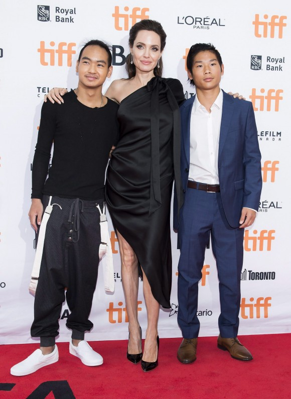 """(L-R) Maddox Jolie-Pitt, Angelina Jolie, and Pax Jolie-Pitt pose on the red carpet for the movie """"First They Killed My Father"""" during the Toronto International Film Festival on Sept. 11, 2017. (THE CANADIAN PRESS/Nathan Denette)"""