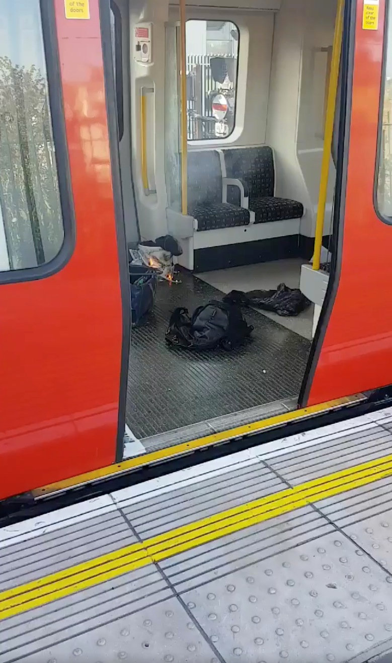 Personal belonglongs and a bucket with an item on fire inside it, are seen on the floor of an underground train carriage at Parsons Green station in West London, Britain on Sept. 15, 2017, in this image taken from social media. (SYLVAIN PENNEC/via REUTERS)
