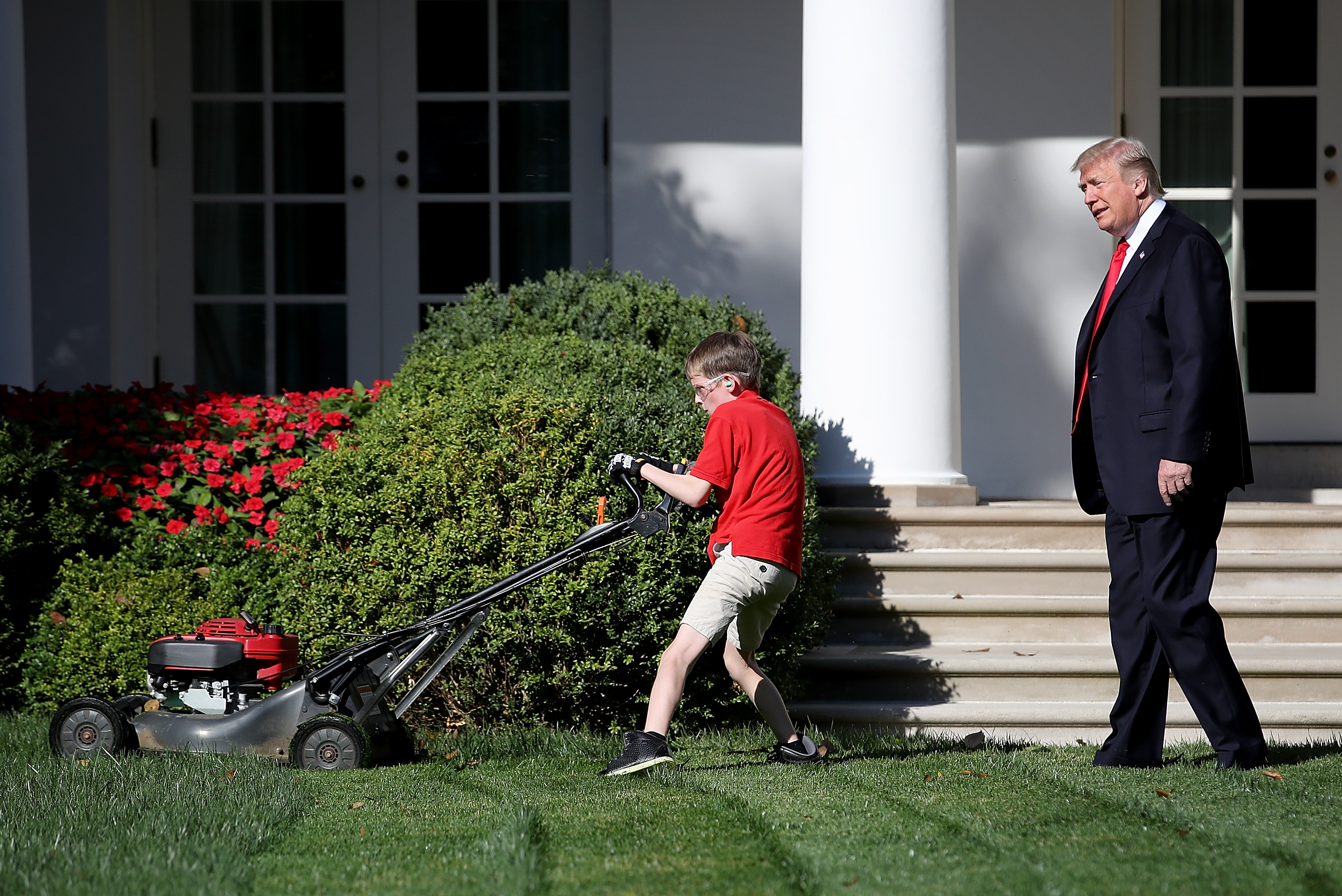 """WASHINGTON, DC - SEPTEMBER 15: U.S. President Donald Trump (R) watches as 11-year-old Frank """"FX"""" Giaccio (L) mows the grass in the Rose Garden of the White House September 15, 2017 in Washington, DC. Giaccio, from Falls Church, Virginia, who runs a business called FX Mowing, wrote a letter to Trump expressing admiration for Trump's business background and offered to mow the White House grass. (Photo by Win McNamee/Getty Images)"""