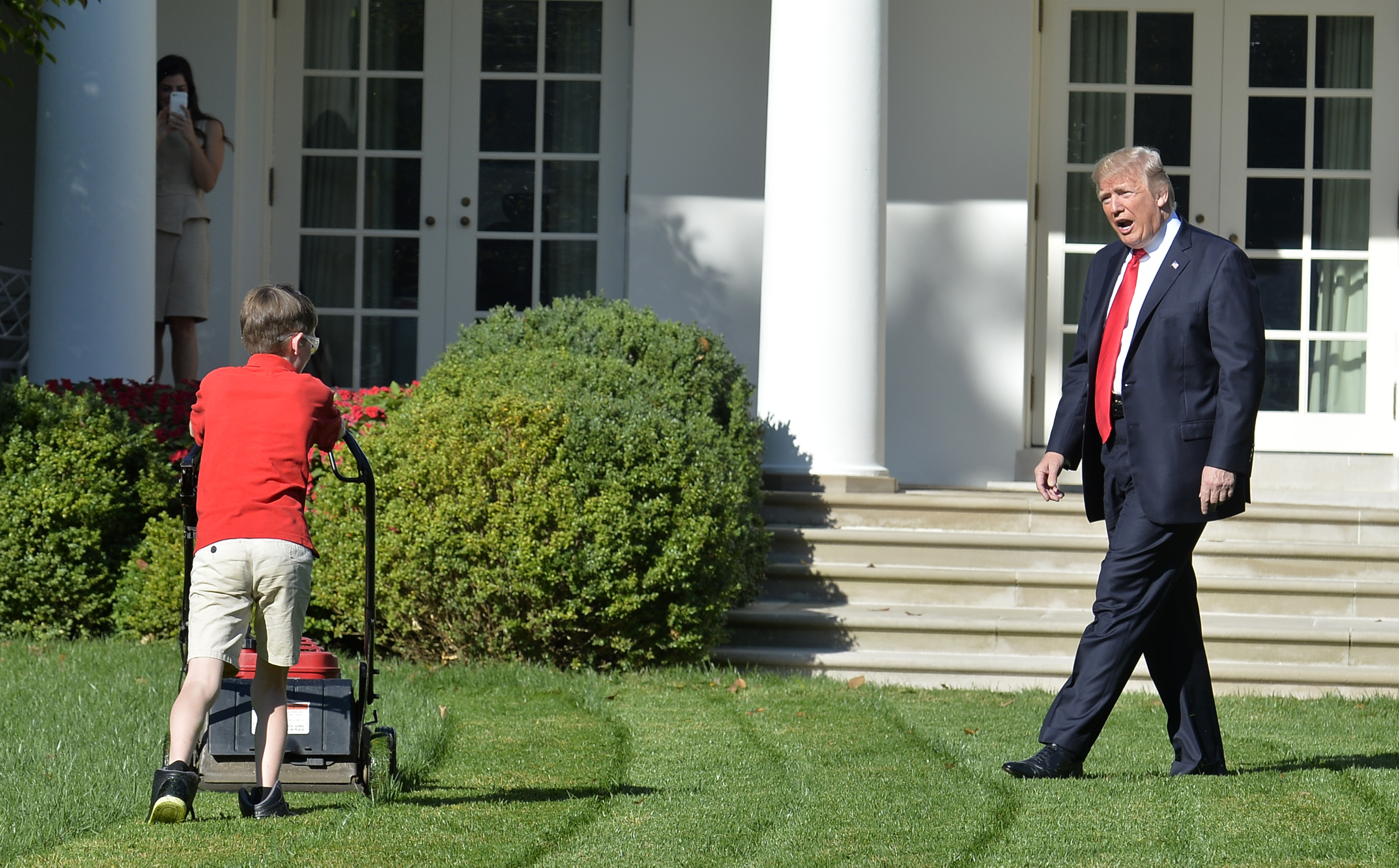 US President Donald Trump watches Frank Giaccio, 11, of Falls Church, Virginia, as he mows the lawn in the Rose Garden of the White House on September 15, 2017, in Washington, DC. Giaccio, who has his own lawn mowing business wrote a letter to the President asking if he could mow the lawn at the White House. / AFP PHOTO / Mike Theiler (Photo credit should read MIKE THEILER/AFP/Getty Images)