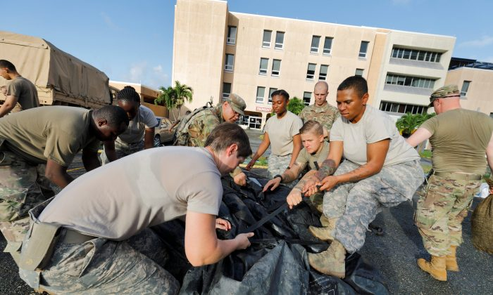 Soldiers from the 602nd Area Support Medical Company secure a portable tent as they break down a field hospital outside the Schneider Regional Medical Center while preparing to evacuate their unit in advance of Hurricane Maria, in Charlotte Amalie, St. Thomas, U.S. Virgin Islands, on Sept. 17, 2017. (REUTERS/Jonathan Drake)