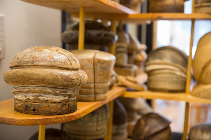 Antique wooden hat blocks which are used to shape the hats are on shelves at the Jennifer Ouellette studio. (Benjamin Chasteen/The Epoch Times)