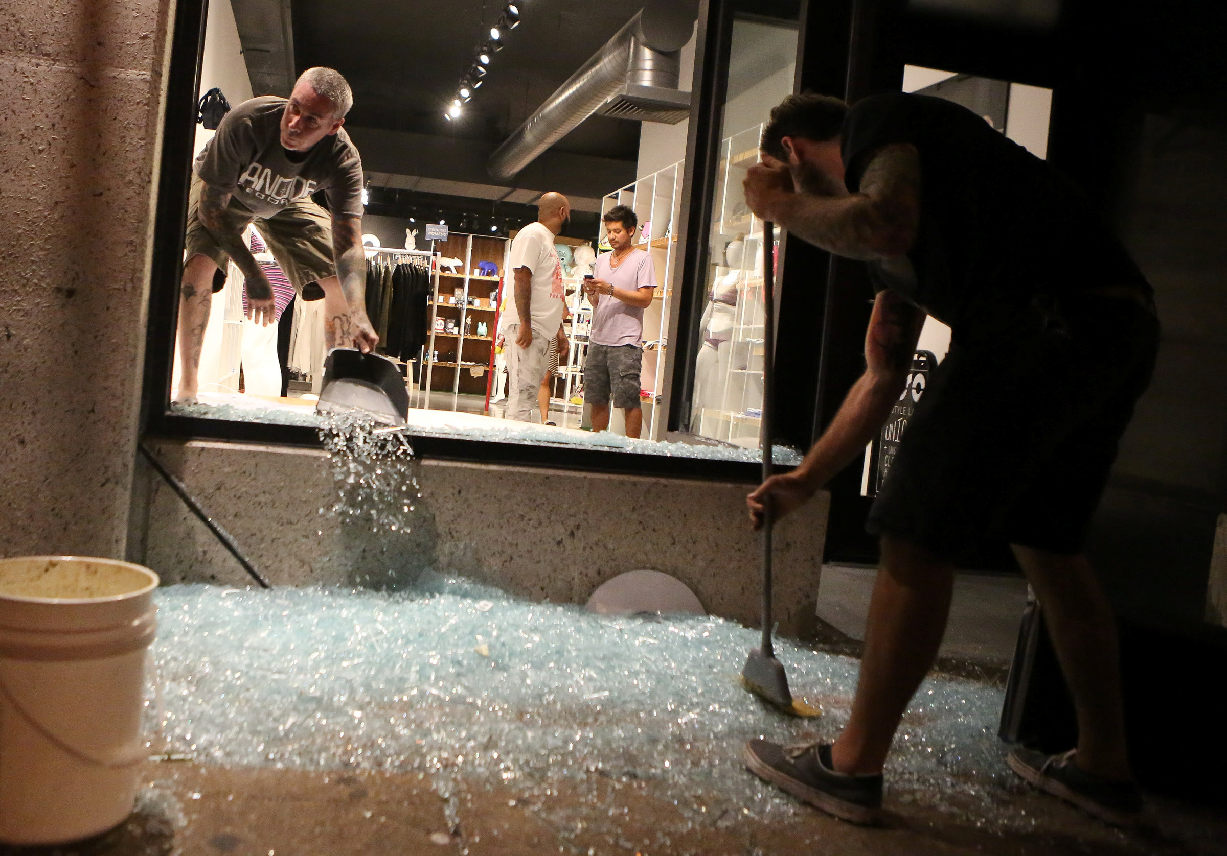 Shopkeepers clean up shattered glass during the second night of demonstrations after a not guilty verdict in the murder trial of former St. Louis police officer Jason Stockley, charged with the 2011 shooting of Anthony Lamar Smith, who was black, in St. Louis, Missouri on Sept. 16, 2017. (REUTERS/Lawrence Bryant)