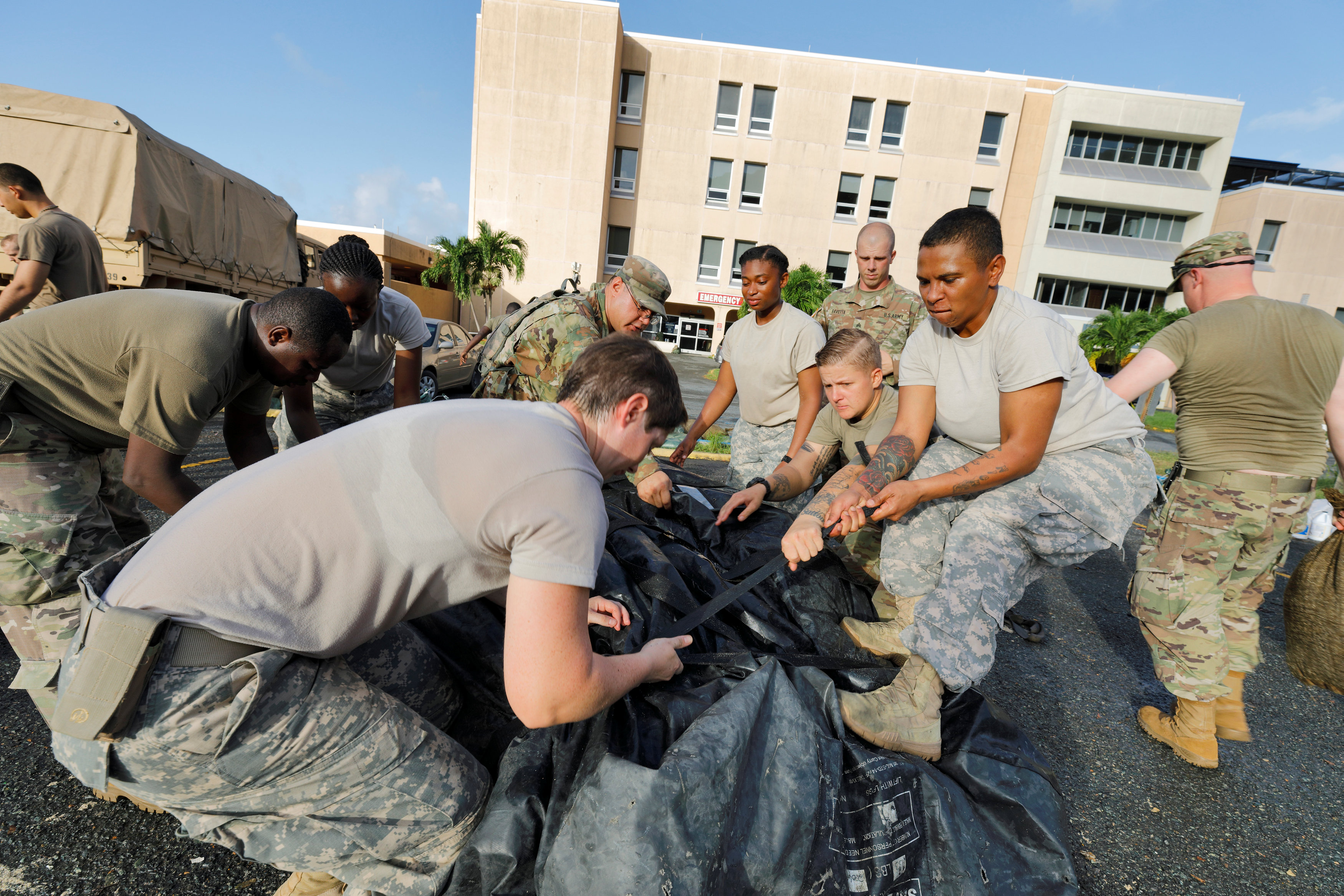 Soldiers from the 602nd Area Support Medical Company secure a portable tent as they break down a field hospital outside the Schneider Regional Medical Center while preparing to evacuate their unit in advance of Hurricane Maria, in Charlotte Amalie, St. Thomas, U.S. Virgin Islands on Sept. 17, 2017. (REUTERS/Jonathan Drake)