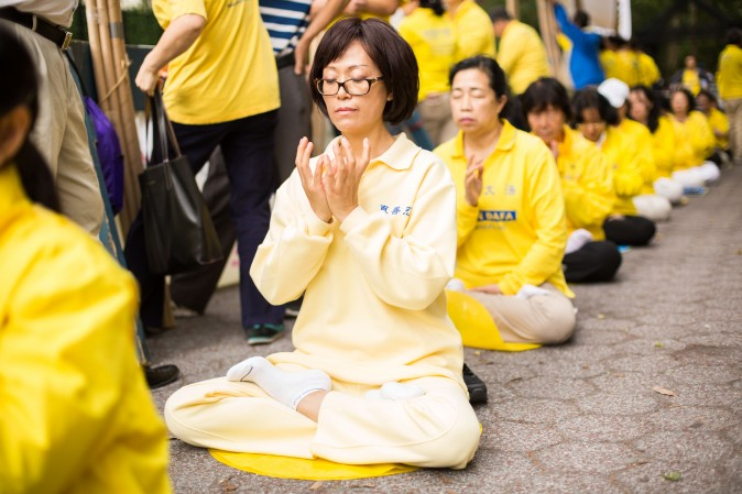 Falun Gong practitioners meditate to raise awareness about the persecution inside China that is now in its 18th year at the Dag Hammarskjold Plaza near the United Nations headquarters in New York while the world leaders meet on Sept. 19, 2017. (Benjamin Chasteen/The Epoch Times)