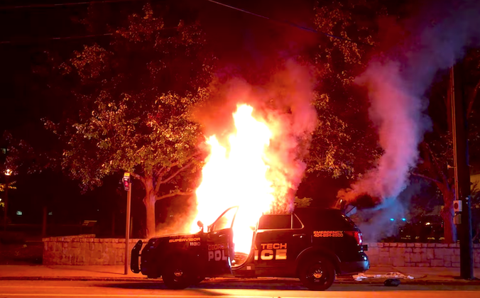 Protesters burn a police car at Georgia Tech on Monday in the wake of the death of student Scout Schultz, who was shot by police when he repeatedly approached them with a knife. (Screenshot via YouTube)