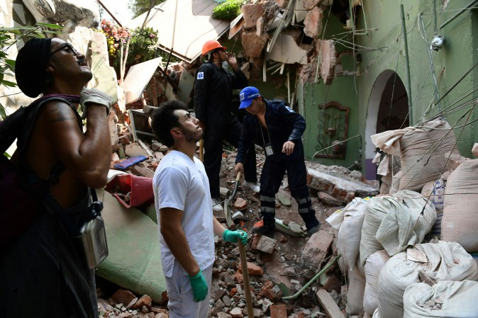 People remove debris from a collapsed building after a quake rattled Mexico City on Sept. 19, 2017.  (RONALDO SCHEMIDT/AFP/Getty Images)