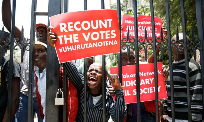 Supporters of Kenya's President Uhuru Kenyatta carry placards as they demonstrate outside the Supreme Court in protest of the nullification of Kenyatta's victory by the Supreme Court Judges in Nairobi, Kenya, September 19, 2017. (Reuters/Baz Ratner)