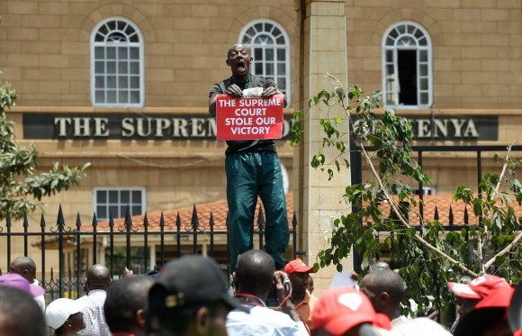 A supporter of Kenya's President Uhuru Kenyatta carries a placard as they demonstrate outside the Supreme Court in protest of the nullification of Kenyatta's victory by the Supreme Court Judges in Nairobi, Kenya, September 19, 2017. (Reuters/Baz Ratner)
