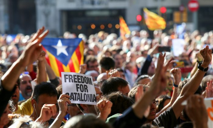 A crowd of protesters gather outside the Catalan region's economy ministry after junior economy minister Josep Maria Jove was arrested by Spanish police during a raid on several government offices, in Barcelona, Spain, September 20, 2017. (Reuters/Albert Gea)