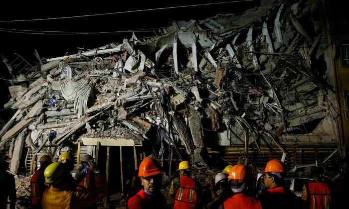 Rescuers work at the site of a collapsed building Sept. 20, 2017 after an earthquake shook Mexico City, Mexico, the day before.   (Reuters/Henry Romero)