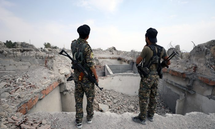 Fighters from Syrian Democratic Forces (SDF) stand near destroyed Uwais al-Qarni shrine in Raqqa, Syria on Sept. 16, 2017. (Reuters/Rodi Said)