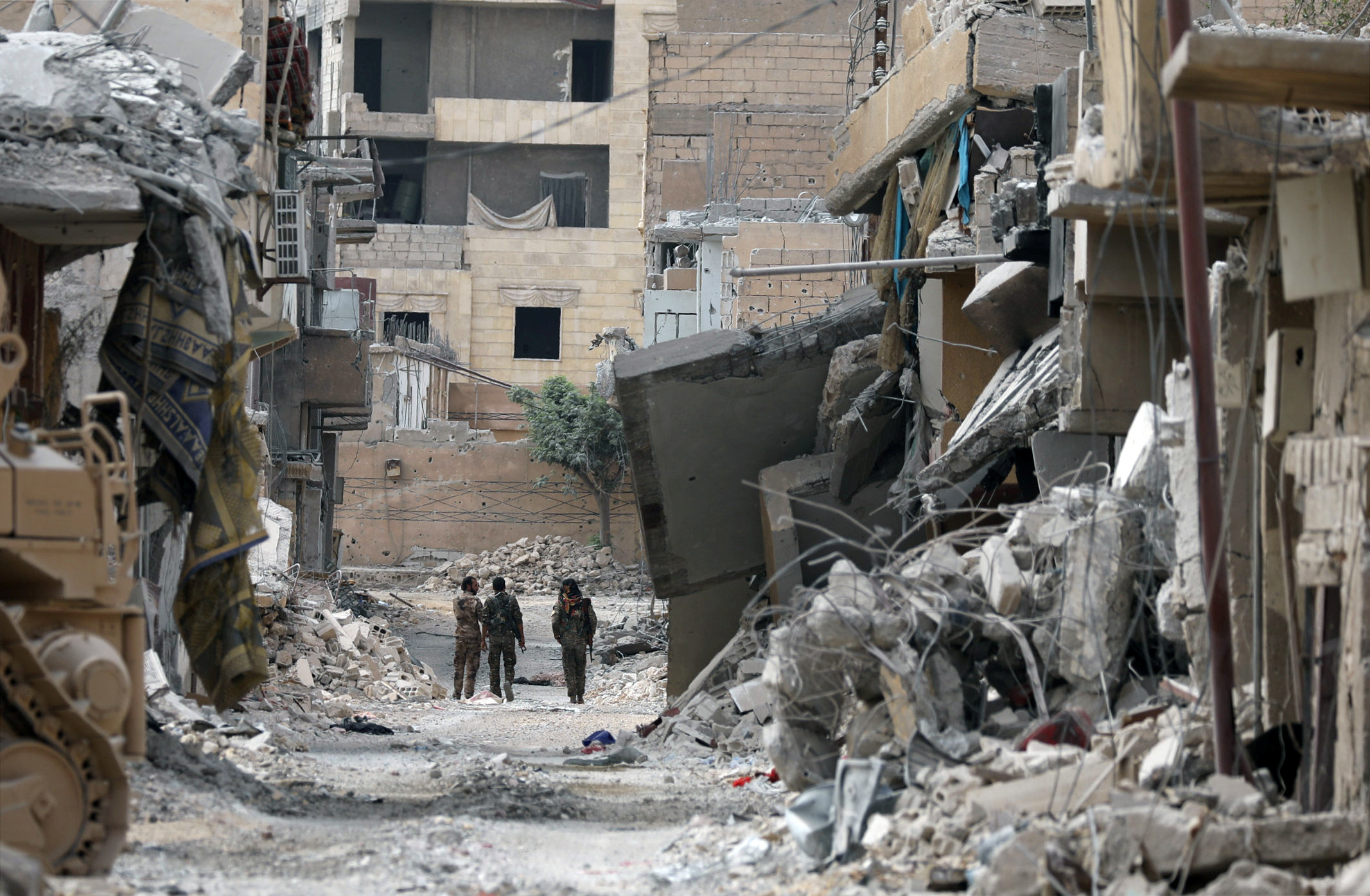 Fighters from Syrian Democratic Forces (SDF) walk together along a damaged street in Raqqa, Syria on Sept. 16, 2017. (REUTERS/ Rodi Said)