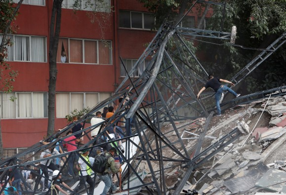 People climb over the debris of a collapsed building after an earthquake hit Mexico City, Mexico, Sept. 19, 2017. (Reuters/Ginnette Riquelme)