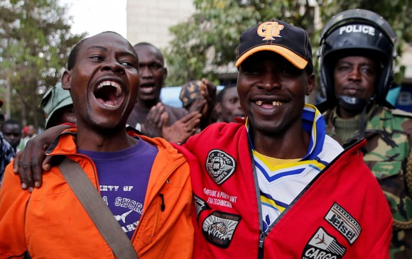 National Super Alliance (NASA) coalition supporters laugh and cheer as they are followed by police near Kenya's Supreme Court In Nairobi, Kenya September 20, 2017. (Reuters/Thomas Mukoya)