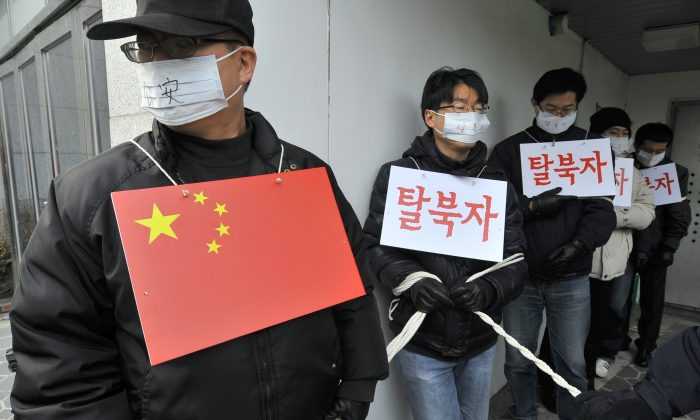 The photo shows rights activists performing the roles of Chinese police and North Korean refugees outside the Chinese Embassy in Seoul on Feb. 21, 2012 during a rally demanding that Beijing scrap plans to repatriate arrested refugees from North Korea. The Chinese regime has intensified its crackdown on North Koreans who attempt to escape the Kim regime through China. (JUNG YEON-JE/AFP/Getty Images)