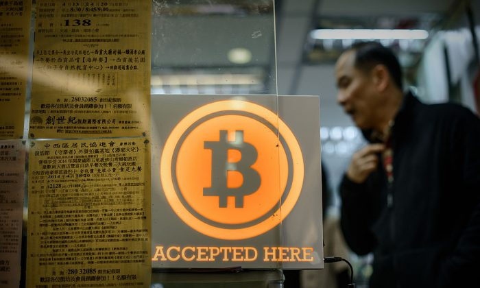 A man walks out of a shop displaying a bitcoin sign during the opening ceremony of the first bitcoin retail shop in Hong Kong on Feb. 28, 2014. (PHILIPPE LOPEZ/AFP/Getty Images)