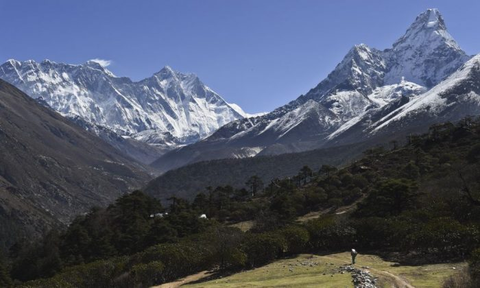 A Nepalese porter carries goods along a pathway in the Himalayas, with Mount Everest on the left, in the village of Tembuche in the Khumbu region of northeastern Nepal on April 20, 2015. (Roberto Schmidt/AFP/Getty Images)
