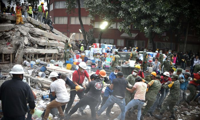 Rescuers, firefighters, policemen, soldiers, and volunteers search for survivors in a flattened building in Mexico City on Sept. 20, 2017, a day after a strong quake hit central Mexico. (YURI CORTEZ/AFP/Getty Images)