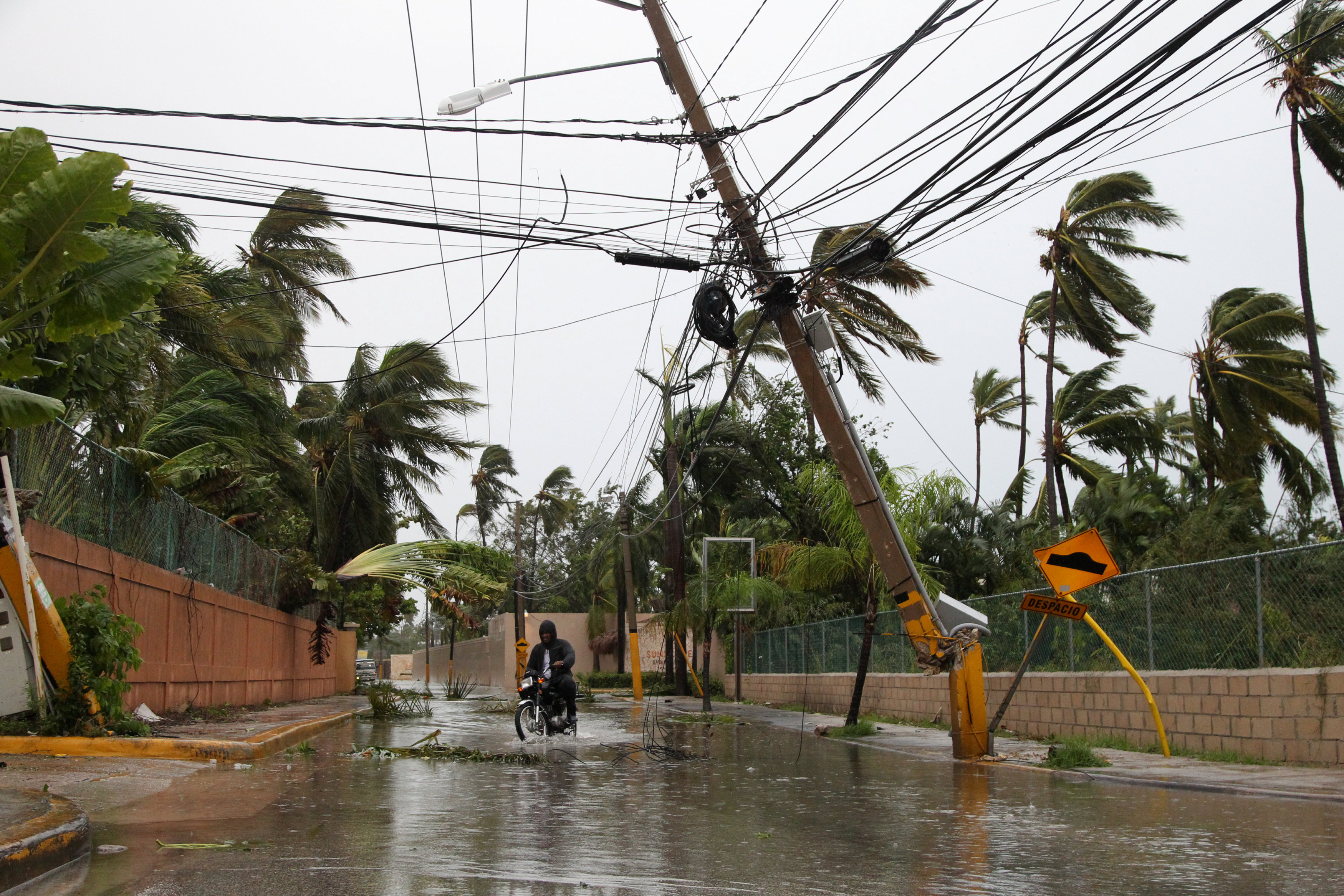 A man rides a motorbike on a flooded street in Punta Cana, Dominican Republic on Sept. 21, 2017. (REUTERS/Ricardo Rojas)
