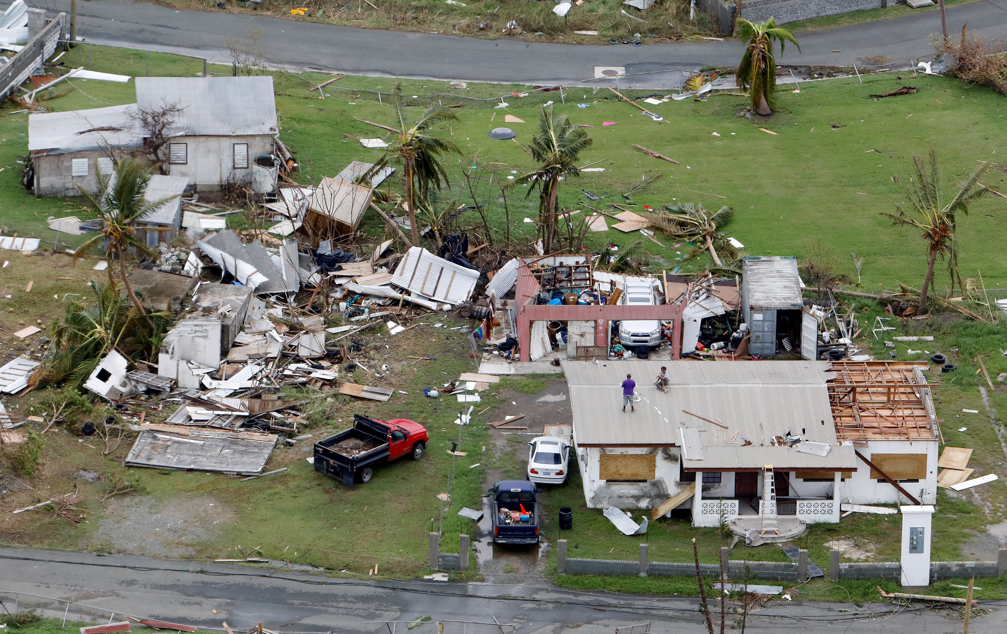 Residents working on their roof in badly damaged neighborhood are seen from a Marine Corps MV-22 Osprey surveying the aftermath from Hurricane Maria in St. Croix, , U.S. Virgin Islands on Sept. 21, 2017. (REUTERS/Jonathan Drake)