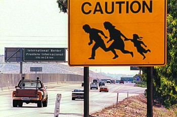 A sign warning drivers about illegal immigrants running across the highway near the U.S.–Mexico border in San Diego on Aug. 9, 1997. (HECTOR MATA/AFP/GETTY IMAGES)