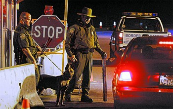 Border Patrol agents prepare to question a motorist at a checkpoint along Highway 94 near Campo, Calif., on Oct. 17, 2007. (SANDY HUFFAKER/GETTY IMAGES)