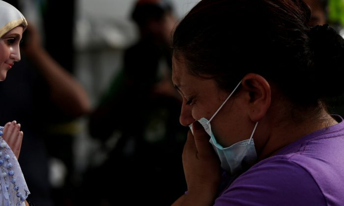 A relative prays to Our Lady of Fatima during a search for survivors in a collapsed building after an earthquake, at Roma neighborhood in Mexico City, Mexico on Sept. 23, 2017. (REUTERS/Carlos Jasso)