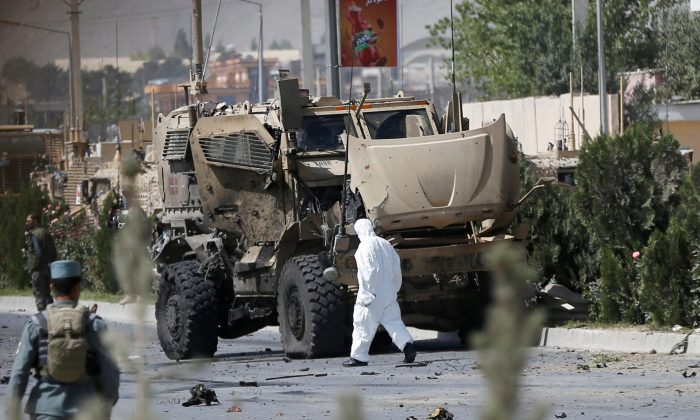 An Afghan official investigates a damaged Danish convoy at the site of a car bomb attack in Kabul, Afghanistan September 24, 2017.  (Reuters/Omar Sobhani)