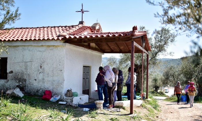 Eritrean and Ethiopian Christian refugees pray outside a small Orthodox church near the Moria migrant camp on the Greek island of Lesbos on March 28, 2017.