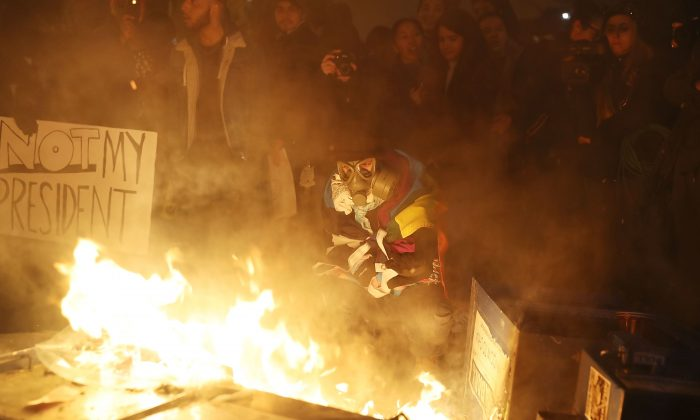 Protesters gather around a fire they started in the street following the inauguration of President Donald Trump in Washington, DC, on Jan. 20, 2017. (Joe Raedle/Getty Images)