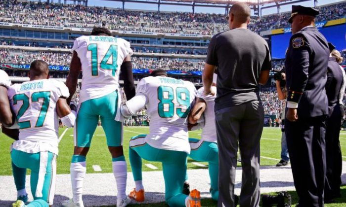 Maurice Smith No. 27 and Julius Thomas No. 89 kneel with Jarvis Landry No. 14 of the Miami Dolphins during the national anthem prior to an NFL game against the New York Jets at MetLife Stadium in East Rutherford, N.J., on Sept. 24, 2017. (Steven Ryan/Getty Images)